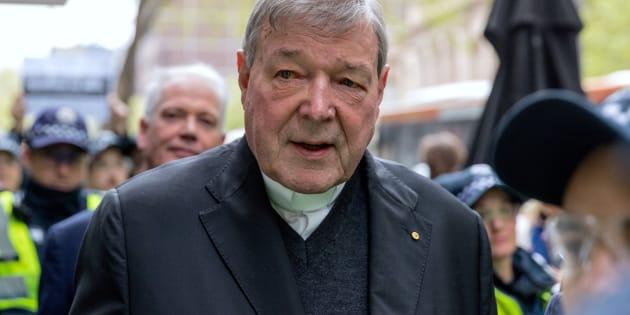 El cardenal australiano George Pell es rodeado por la policía australiana mientras sale de la corte de magistrados de Melbourne en Australia.