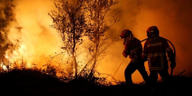 Una pareja de bomberos trata de apagar las llamas en el foco de Cabanoes, cerca de Lousa, Portugal, el pasado lunes.