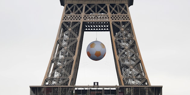 A soccer ball is suspended under the Eiffel Tower before the start of the UEFA 2016 European Championship in Paris, France, June 3, 2016. REUTERS/Charles Platiau