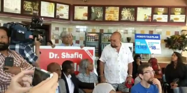 Ontario Liberal candidate Shafiq Qaadri appeared at an NDP press conference holding one of his campaign signs.