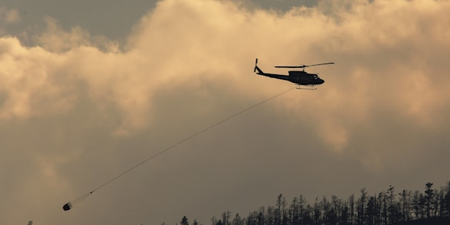 A helicopter flies over a wildfire south west of the town of Cache Creek, British Columbia on July 18, 2017.