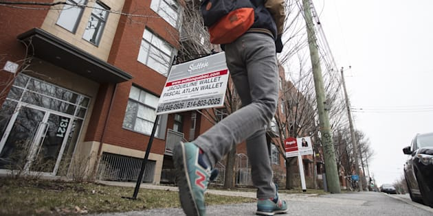 A pedestrian passes in front of a home for sale in the Le Plateau Mont-Royal borough of Montreal on April 14, 2018.