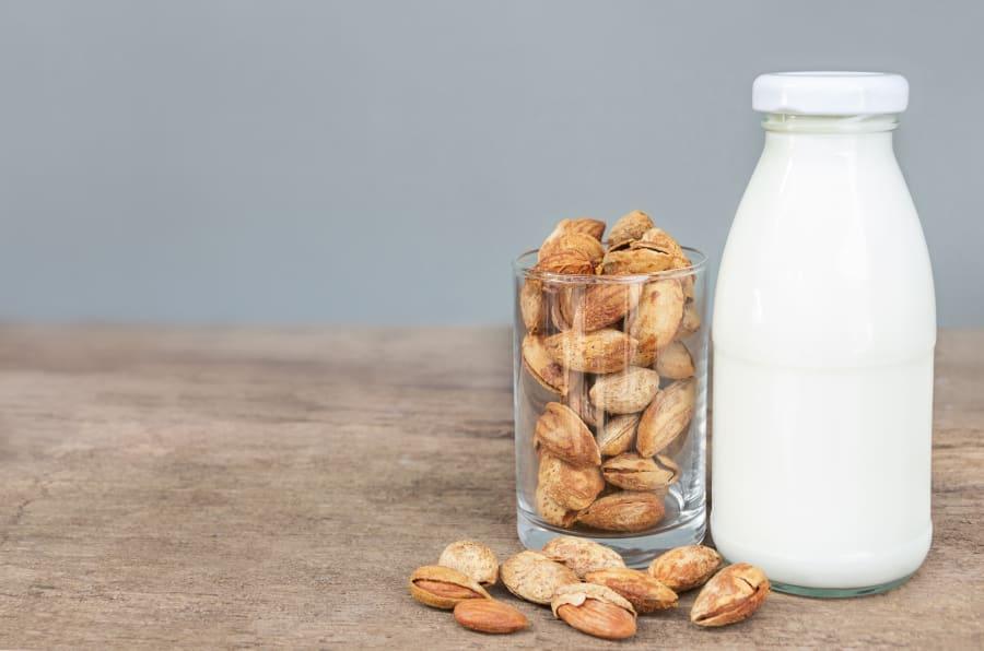 Imagen de un vaso con almendras junto a un vaso de leche, ¿cuál es mejor?