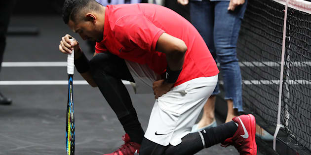 Nick Kyrgios drops to one knee before his match against Roger Federer.
