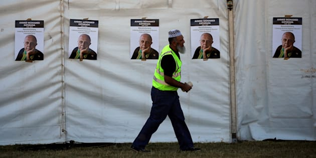 A worker walks past posters bearing the face of anti-apartheid activist Ahmed Kathrada, who was sentenced to life imprisonment alongside Nelson Mandela, ahead of his funeral at the Westpark Cemetery.