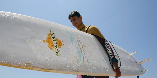 Ali Kassem, 17 ans, réfugié syrien, avec sa planche de surf sur une plage de la ville de Jiyeh, dans le sud du Liban.