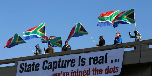 Protesters hang a banner as they hold flags in protest ahead of the African National Congress 5th National Policy Conference at the Nasrec Expo Centre in Soweto, South Africa, June 30, 2017.  REUTERS/Siphiwe Sibeko