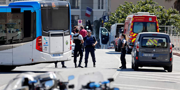 French police secure the area where one person was killed and another injured after a car crashed into two bus shelters.