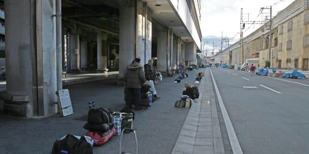 あいりん労働福祉センター前に荷物を置き、日雇労働のあっせんを待つ人たち。日雇い労働者が集まるこの地域には、彼らが泊まる簡易宿泊所が多い=大阪市西成区