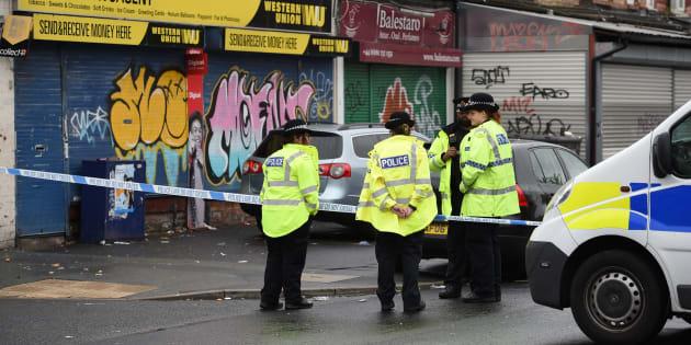 発砲現場で警戒態勢をとる警察官=2018年8月12日、英・マンチェスター南部のモスサイド