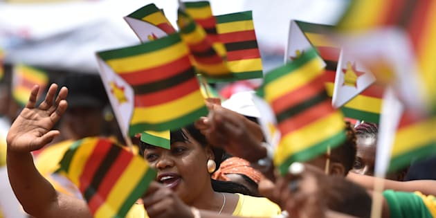 People react as Zimbabwe's President Emmerson Mnangagwa is sworn-in during a ceremony in Harare on November 24, 2017.
