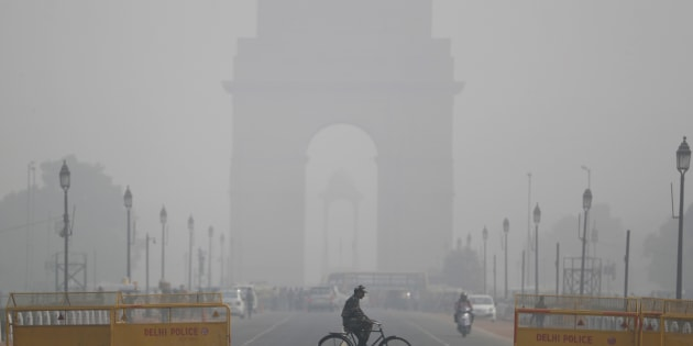 An Indian soldier rides a bicycle as past the India Gate monument on a fog enveloped morning in New Delhi, India, Thursday, Dec. 1, 2016. A thick blanket of fog engulfed Delhi, the national capital region and much of northern India, disrupting road, rail and air traffic. (AP Photo/Altaf Qadri)