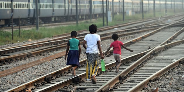 Indian children walk along the railway tracks after defecating in the open on International Toilet Day.