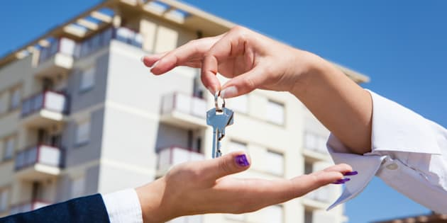 Realtor is giving the keys to an apartment to some clients aa focus on the keys