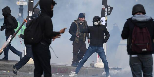 Un manifestant jette un projectile vers la police lors de la manifestation du 1er mai à Paris.