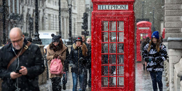 LONDON, UNITED KINGDOM - JANUARY 13: Tourists walk past a red phone box as snow falls on Parliament Square on January 13, 2017 in London, United Kingdom. The Met Office has issued a yellow 'be aware' warning for much of the country, as snow and high winds are expected to cause disruption until late on Friday.  (Photo by Chris J Ratcliffe/Getty Images)