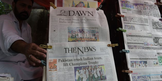 A Pakistani vendor arranges morning newspapers featuring front page coverage of Pakistan's victory against India in the ICC Champions Trophy final cricket match played in London.