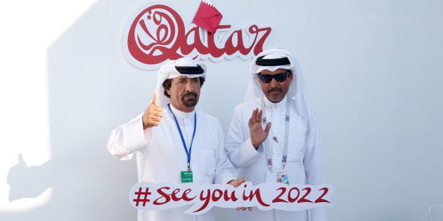 """Dos hombres muestran un letrero con la leyenda de """"Catar 2022""""."""