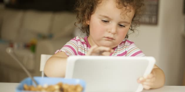 cute little girl eating cornflakes and playing on digital tablet