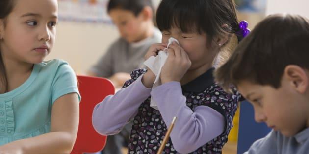 Une jeune élève se mouche dans une classe.