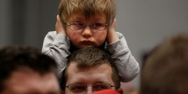 A child covers his ears before Republican presidential nominee Donald Trump appears at a campaign rally in Sioux City, Iowa, U.S. November 6,  2016.