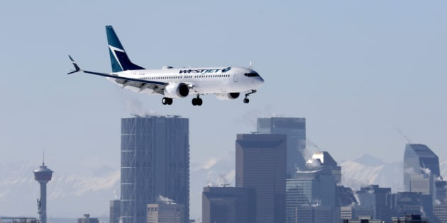 A Boeing 737 MAX 8 jetliner, belonging to WestJet Airlines, passes the downtown skyline as it lands in Calgary, Alberta on March 3, 2019.
