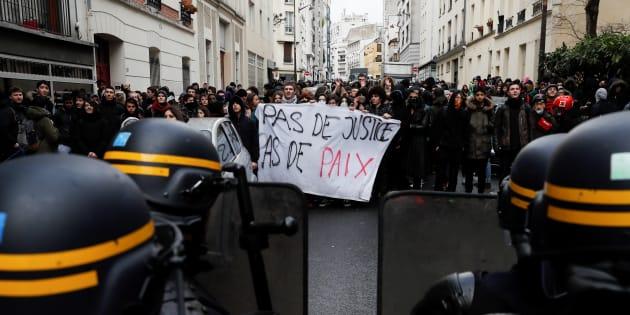 """Des étudiants brandissent le slogan """"Pas de police, pas de paix"""" face à la police anti-émeute le 28 février 2017 à Paris, trois semaines après l'affaire Théo."""