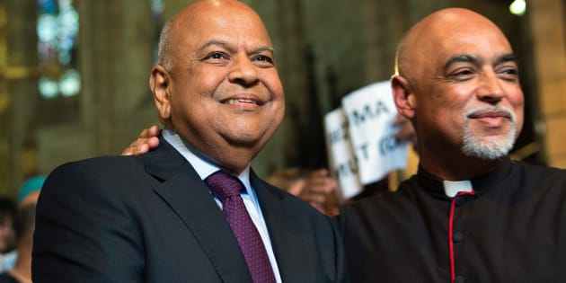 Pravin Gordhan, (L) the recently dismissed South African Minister of Finance, stands next to Reverend Michael Wheeder (R)  at a memorial service for recently deceased anti-apartheid activist Ahmed Kathrada at St George's Cathedral in Cape Town on April 6, 2017.