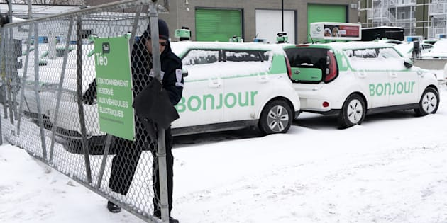 A security guard closes the gate of a parking lot of Teo Taxi in Montreal on Jan. 29, 2019. Montreal's Teo Taxi, which sought to take on Uber with a fleet of electric vehicles, has halted operations and laid off all its drivers.