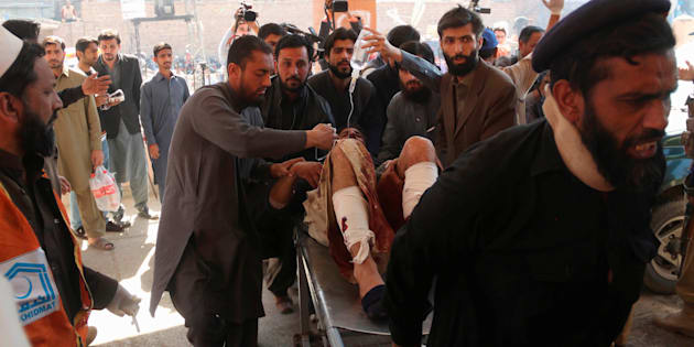 Hospital workers transport a man injured in the Charsadda blast to the hospital in Peshawar, Pakistan February 21, 2017.