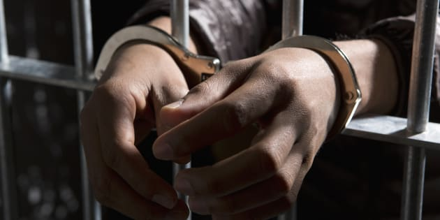 An inmate's hands are seen in handcuffs.