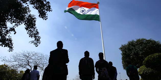 People stand for national anthem during the hoisting of the largest national flag, measuring 60 ft x 90ft, atop a 207 ft flag pole at Rajiv Chowk on 7 March 2014 in New Delhi, India. (Photo by Ajay Aggarwal/Hindustan Times via Getty Images)