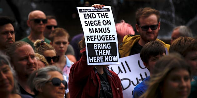 Refugee advocates hold placards as they participate in a protest in Sydney, Australia, against the treatment of asylum-seekers.