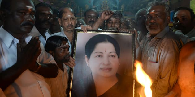 Supporters hold a photograph of Tamil Nadu state leader Jayalalithaa Jayaram.