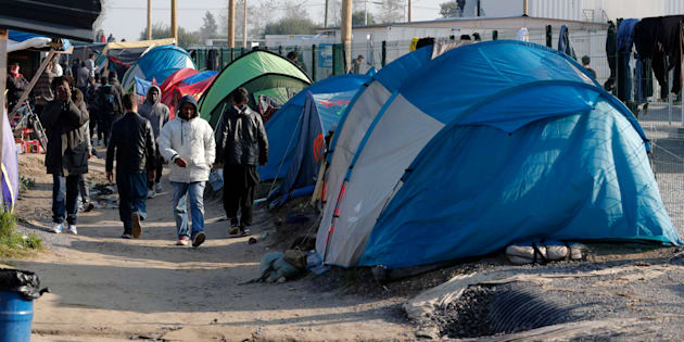 """Migrants walk in an alley near tents and makeshift shelters on the eve of the evacuation and dismantlement of the camp called the """"Jungle"""" in Calais, France, October 23, 2016."""