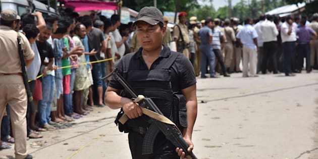 An Indian security personal stands guard near the site of a militant attack on a market at Balajan Tinali in Kokrajhar District, Assam