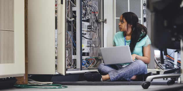 Female student checking on network servers using a laptop.