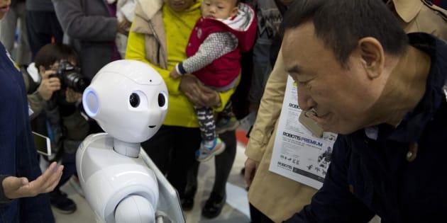 Le robot Pepper et des visiteurs de la World Robot Conference de Pekin en Chine, le 21 octobre 2016. (AP Photo/Ng Han Guan)