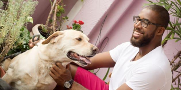 Marcos Madeira brinca com um dos cachorros com quem passeia por São Paulo.
