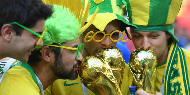 Torcedores brasileiros beijam réplicas da taça da Copa: caminho do hexa é complicado.