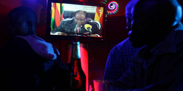 People watch as Zimbabwean President Robert Mugabe addresses the nation on television, at a bar in Harare, Zimbabwe, November 19, 2017. REUTERS/Philimon Bulawayo
