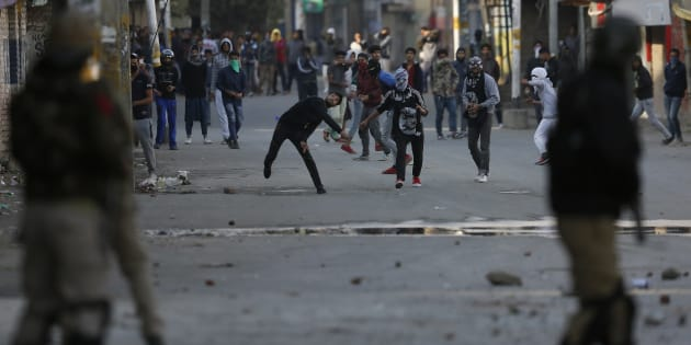Kashmiri protesters throw stones at Indian policemen in Srinagar on Monday.