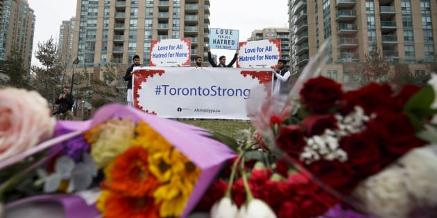 A local Toronto Muslim group holds up signs for love and courage for victims of the April 23 crash, at a memorial on Yonge Street at Finch Avenue on April 24, 2018 in Toronto.