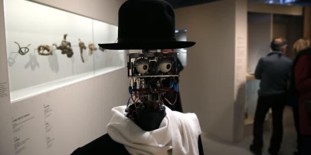 """Le robot Berenson se promène parmi les visiteurs durant l'exposition """"Persona : Étrangement humain"""" au musée du Quai Branly à Paris, le 23 février 2016. Créé en 2011 par l'anthropologue Denis Vidal et l'ingénieur Philippe Gaussier, ce robot expérimental enregistre les réactions des visiteurs aux œuvres d'art pour se les approprier et pouvoir les juger ensuite par lui-même."""