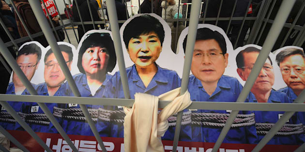 Portraits of South Korea's President Park Geun-Hye (C) and her aides are set in a mock prison during a rally against the scandal-hit president in central Seoul on December 17, 2016.