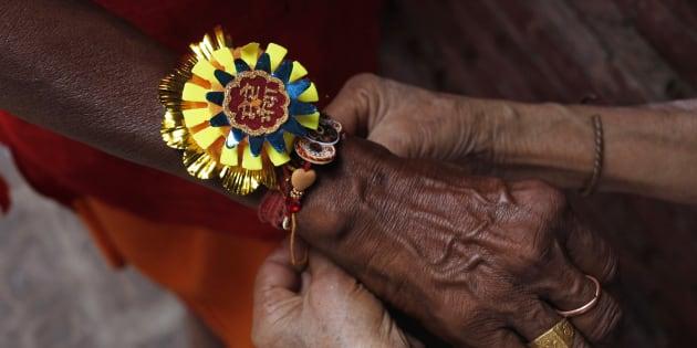 "Jamuna Devi, 85, a widow ties a ""Rakhi"" on the wrist of a Hindu holy man"