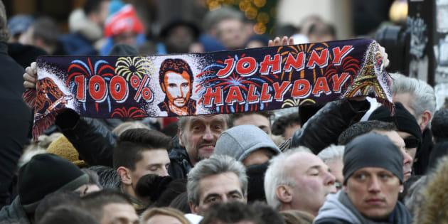 Un fan de Johnny Hallyday tendant une écharpe du chanteur à la Madeleine le 9 décembre 2017