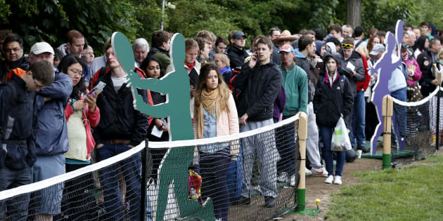 Members of the public queue to enter the grounds on the first day of the All England Lawn Tennis Championships at Wimbledon, England, Monday, June 24, 2013. (AP Photo/Sang Tan)