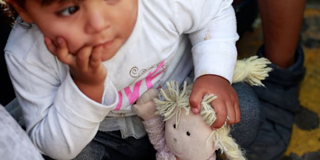 A member of a migrant family from Mexico, fleeing from violence, holds her doll while waiting to enter the United States to meet officers of the U.S. Customs and Border Protection on June 20.