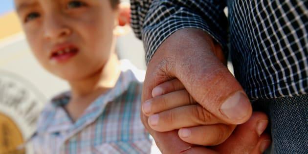 El emigrante salvadoreño Epigmenio Centeno sostiene la mano de su hijo de tres años Steven Atonay afuera del albergue House of the Migrant, luego de que decidió quedarse con sus hijos en México debido a la política de separación de niños del presidente estadounidense Donald Trump en Ciudad Juárez.